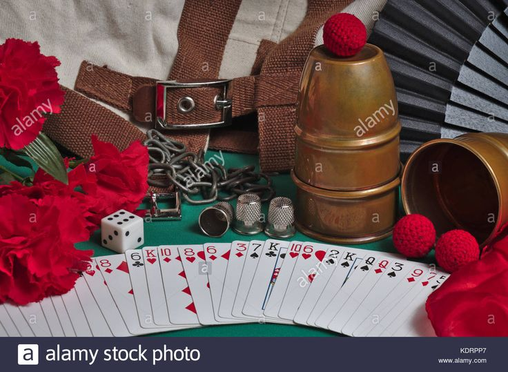 Download this stock image: Classic props used by Magicians. Cups and balls, flowers, chains, straight jacket, silk handkerchiefs, thimbles dice, fan, and poker playing cards - KDRPP7 from Alamy's library of millions of high resolution stock photos, illustrations and vectors.