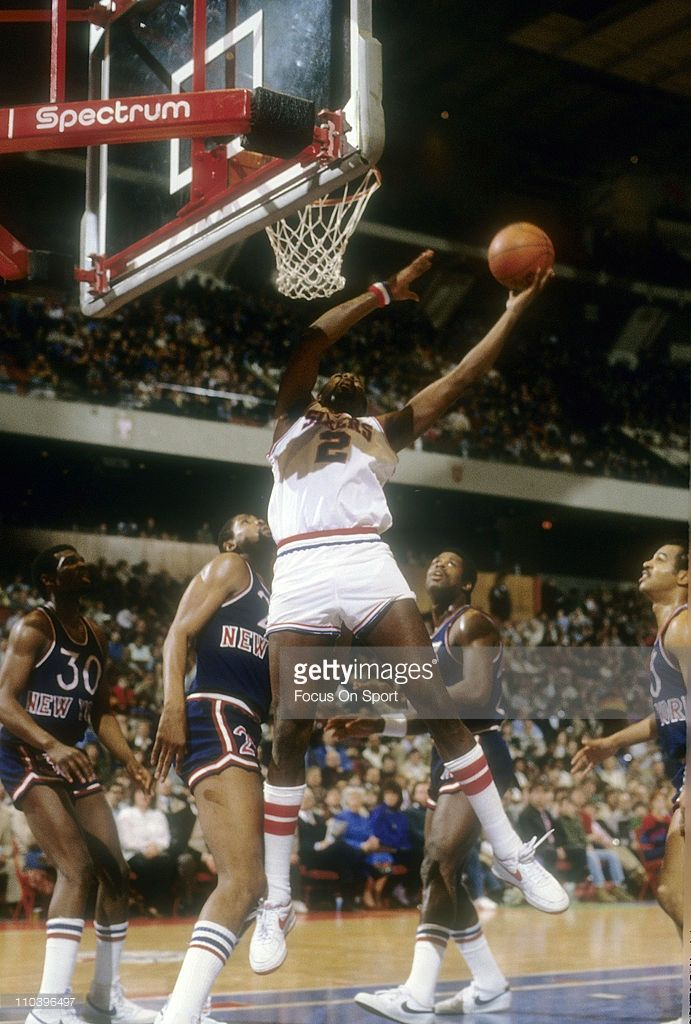 Moses Malone #2 of the Philadelphia 76ers grabs a rebound against the New York Knicks during an NBA basketball game circa 1984 at the Spectrum in Philadelphia, Pennsylvania. Malone played for the 76ers from 1982-86 and 1993-94.