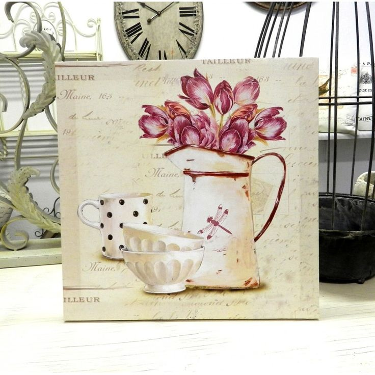 Kwadratowy obraz prowansalski na którym znajdują się różowe tulipany w starodawnym metalowym naczyniu, kubek oraz miseczki. Całość ozdabia tło w kremowym kolorze z delikatnymi napisami.