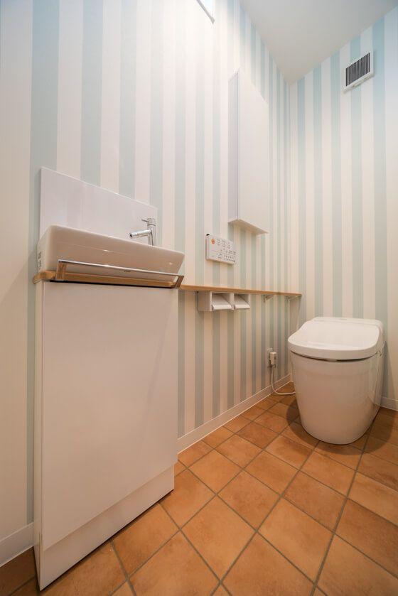 洗濯室の横のトイレは、ストライプ柄のクロス(品番: #RE-2844 )と、テラコッタ風のクッションフロア(品番: #HM-1113 )でコーディネート。 2階はTOTOのタンクレストイレと、手洗いカウンター カウンターは「ミルベージュ」というナチュラルな木目色に、収納は、ストライプのクロスに映えるホワイト色にされました。 #壁紙 #クロス #ストライプ #クッションフロア #CF #テラコッタ