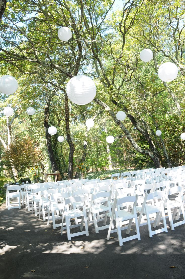 White paper lanterns hanging from trees during an outdoor ceremony in the shade.