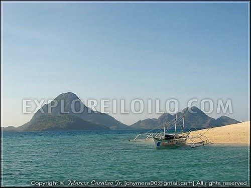 "A motorized boat or ""banca"" docked at the shifting sandbar of Agho Island"