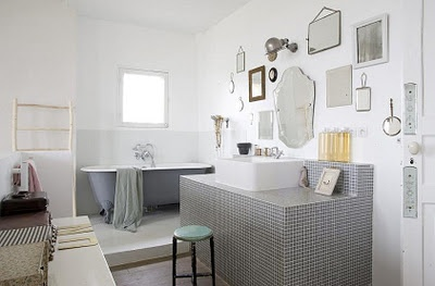 Grey and white bathroom. Loving the vintage mirrors wall!