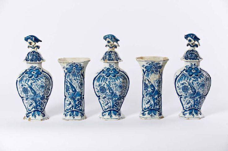 Een Delfts blauw aardewerk vijfdelig kaststel    18e eeuw, gemerkt De Porceleyne Lampetkan  drie balustervormige vazen met deksels bekroond door papegaaien en twee bekervazen, met een decor van een vogel op een bloemenrots in een florale cartouche (beschadigingen en restauraties). (5( H 38 en 27 cm