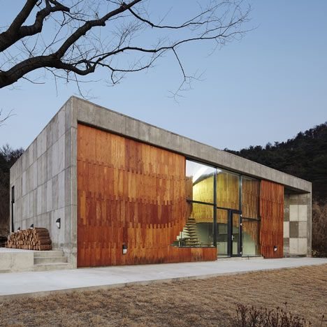 a wall of wooden scales folds through the glazed facade of this house and studio thatKorean architectsANDdesigned for an artist in South Korea.