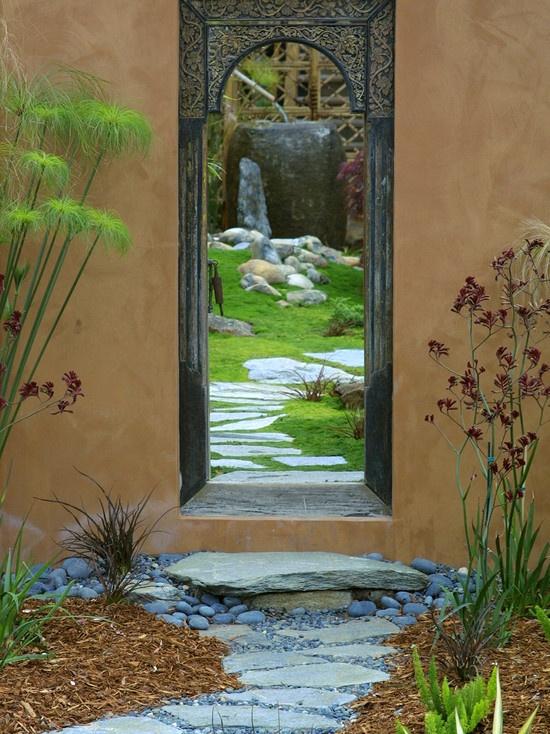 beautiful mirror in garden, looks like a door with doorstep rock, so neat