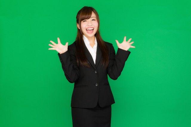 両手を広げて喜ぶスーツ姿の女性(グリーンバック)