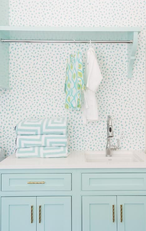 Aqua blue laundry room features aqua blue shaker cabinets adorned with brass pulls topped with white quartz fitted with a white sink and polished nickel faucet.