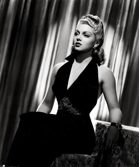 The young Lana Turner is ravishing in the backless, halter-top gown shown below. It is a simple but stunning gown, decorated with embroideries below the bust. Adrian designed this costume for Lana Turner in the Ziegfeld Girl, 1940.While many backless gowns were designed for stars of the silver screen, it is rare to see them photographed from behind. Even in fashion shots and set stills, it was the face of the actress that sold the movie, and thus, that was the money shot for film publicity.