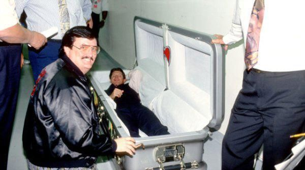 Paul Bearer standing outside the casket that was made for the Undertaker / Warrior match, with Vince McMahon just chilling inside it.