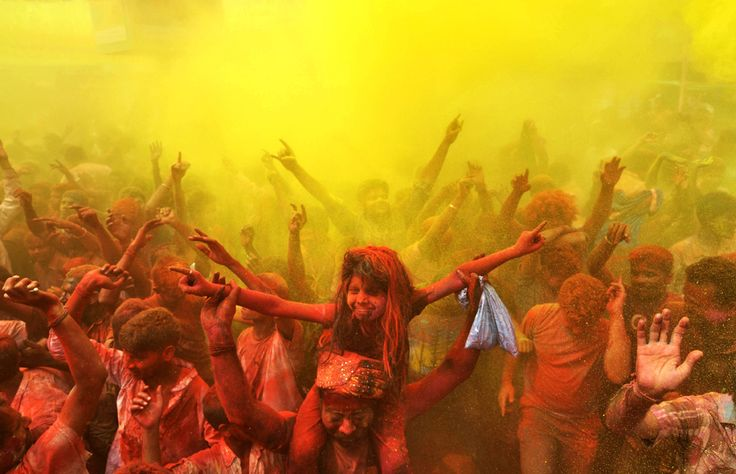 Indian revelers cover each other with colored powder and dance while taking part in Holi festival celebrations in Guwahati on March 17. Holi...