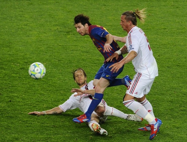 Barcelona's Argentinian forward Lionel Messi (C) fights for the ball with AC Milan's defender Luca Antonini (L) and French defender Philippe Mexes