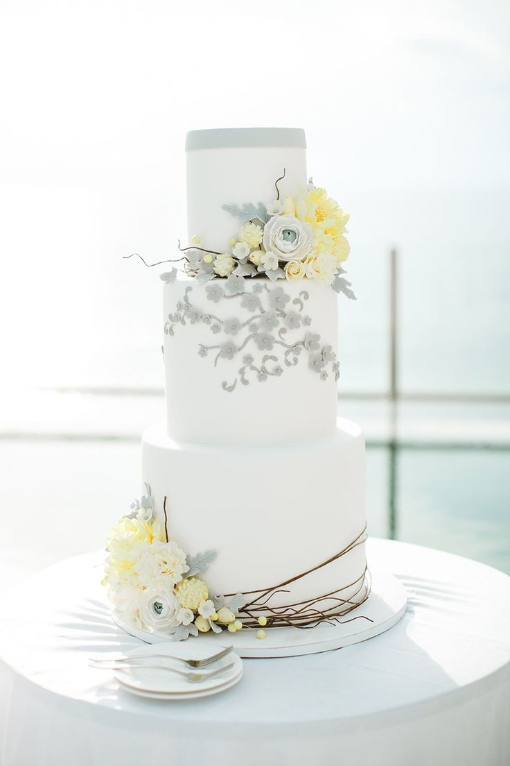 Grey, white and yellow tiered wedding cake with florals {Facebook and Instagram: theweddingscoop}