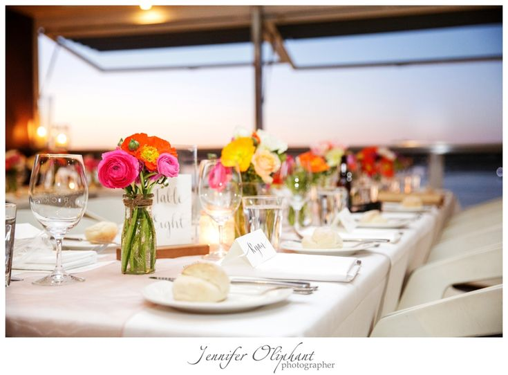 Bright reception designs in jars with ranunculus and poppies. Image by Jennifer Oliphant photography