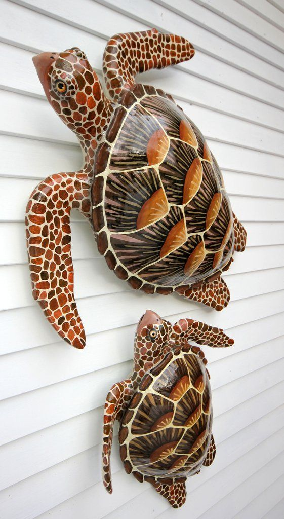 Ancient sages of the sea, sea turtles have inspired humans through the ages. The Fish Collection's Sea Turtle wall art embodies the turtles' steadfast and tranquil nature. This unique folk art features a maternal adult female and her inquisitive baby, which can be purchased together or separately. Both glide as gracefully on a wall as they do in the ocean. The base for their form was created from wood, while their flippers were created from recycled wooden bowls. Clay applied to the surface…