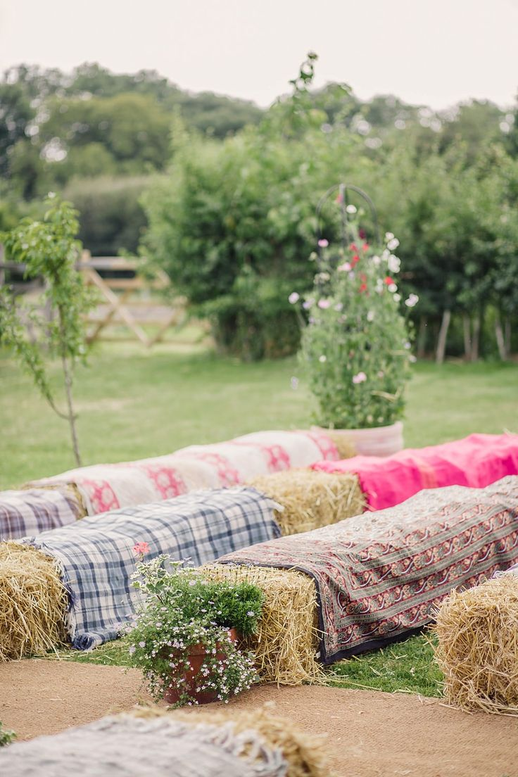 Hay bales as seating for the outdoor wedding ceremony in an English Country Garden -   Image by  Lola Rose Photography - A wedding gown by Enzoani for an English back garden DIY wedding in Surrey. With hand picked flowers and Bridesmaids dresses from French Connection and Alfred Sung. The Groom wears a classic morning suit.