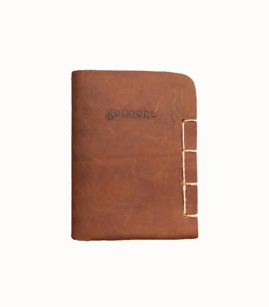 Gouache - Leather Passport Holder Brown. More than just a passport holder, this Gouache piece houses your most sentimental travel tokens. It comfortably holds your passport, with still enough space to tuck documents, photos of home, or your small tokens like plane tickets or bus stubs into the sleeve. Made by an artisan in the Philippines who was forced to leave home due to natural disasters, this piece puts front and centre the skilled craftsmanship of its maker.  Simple, rugged, and…