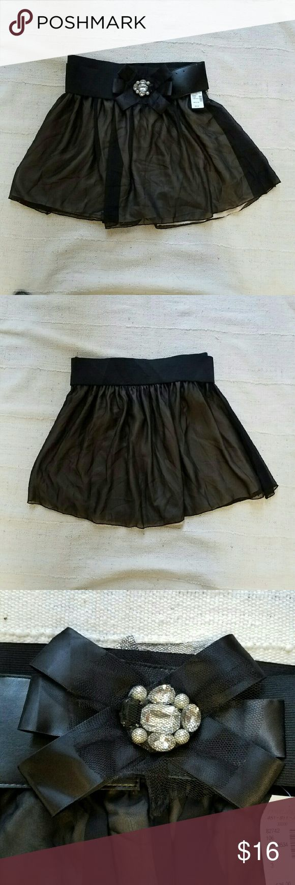 NWT Black Holiday Skirt Bow Front Maurices Cute skirt perfect for Holiday & NYE parties with its bow detail on the belt. Brand new with tags. Has tulle & rhinestone details. Black overlay on top of nude lining. 100% polyester. Size M.  Please check out my closet for more NWT items to bundle with discount and save more with combined shipping. Maurices Skirts Mini