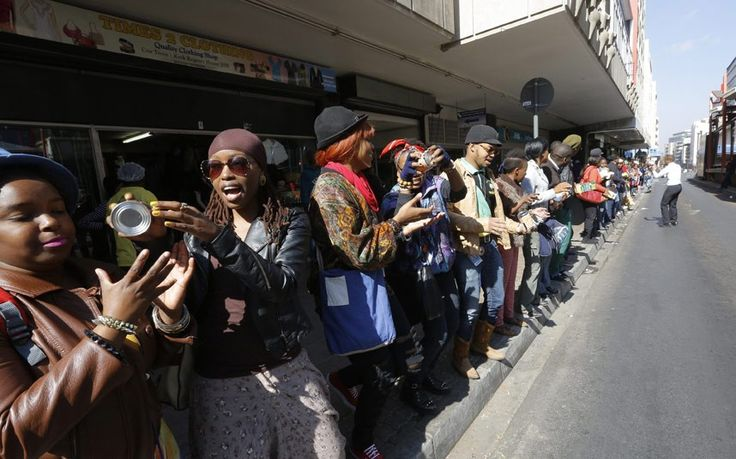 People form a human chain to pass donated food and clothes to a nearby shelter in celebration of Mandela Day in downtown Johannesburg,