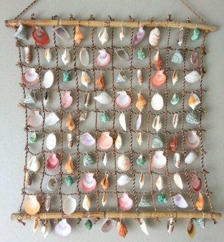 drill seashells and hang them from netting stretched between two pieces of driftwood -