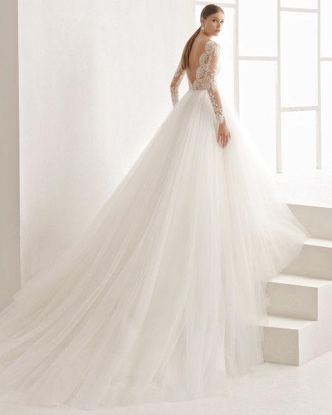Vestido de novia princesa con cuerpo de encaje con transparencia y falda de tul con maxi volumen, escote barco y manga larga, en color natural.