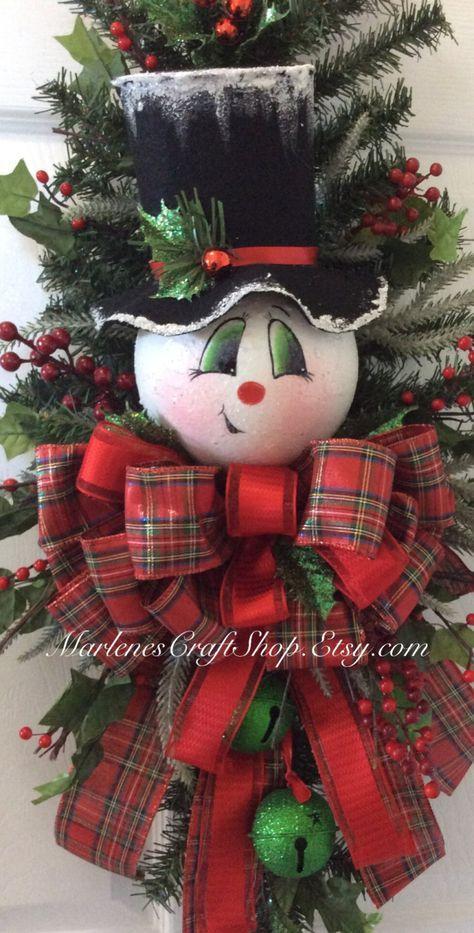 Hier komt Frosty! Hij heeft nogal een grillige uitstraling over hem met zijn krom kleine glimlach ~ ~ ~ hij klaar voor de vakantie! Deze handgeschilderde Snowman deur sawg is versierd met bessen en Plaid lint. Er zijn twee groene jingle bells aangesloten op zijn kraag boog die met de rood en greens coördineren. De rand van zijn hoed is afgestoft met een sparkly besneeuwde afwerking. De metingen zijn ongeveer 34 inches lang en 16 inch breed. Dit is een KLAAR GEMAAKT ITEM…