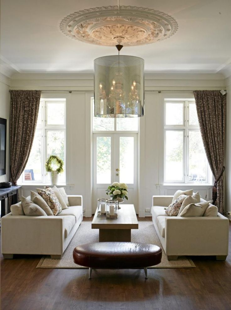 Klassiske møbler fra Slettvoll gir tv-stuen et stilrent preg. Herfra er det en dør ut til en rommelig balkong. Den moderne lysekronen kommer fra italienske Moooi, kjøpt hos Expo Nova. Gardinene er sydd i tekstiler fra Designs of the time, fra Noma interiørtekstiler. Den rødlige skinnpuffen er kjøpt hos Martin Olsen Møbelgalleri.