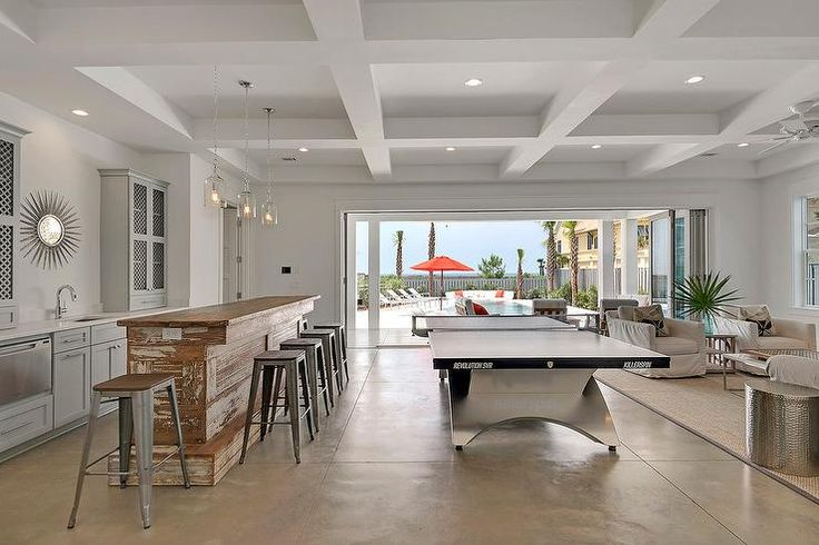 Well appointed beach style game room boasts Corsica 1 Light Pendants hung from a white coffered ceiling over a whitewashed reclaimed wood bar seating five Tolix Stools facing gray wet bar cabinets fitted with a dishwasher, long nickel pulls, and a white quartz countertop holding a sink with a polished nickel gooseneck faucet beneath a silver sunburst mirror flanked by metal lattice cabinets.