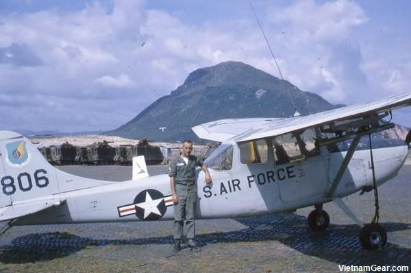 Overlooked by Tuy Hoa's Chop Chai Mountain, MACV advisor Tim Coughlin stands in front of a U.S. Air Force Cessna 0-1 Bird Dog.    Unarmed, expect for marking rockets, the Bird Dog was flown by Forward Air Controllers (FAC) throughout the Vietnam War.    Photo taken: Late 1964