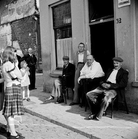 De eigenaar en drie bezoekers voor het café Dikke Dries...1950