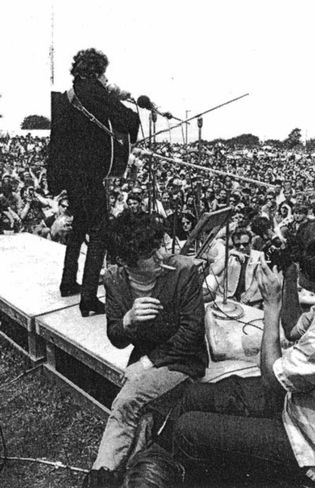 Donovan sitting on stage as Bob as Bob Dylan performs at the Newport Folk Festival 1965