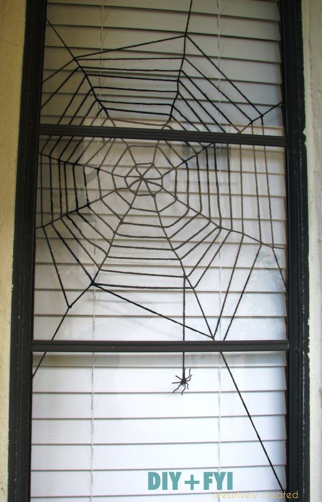 DIY Spider web window decoration using black yarn.