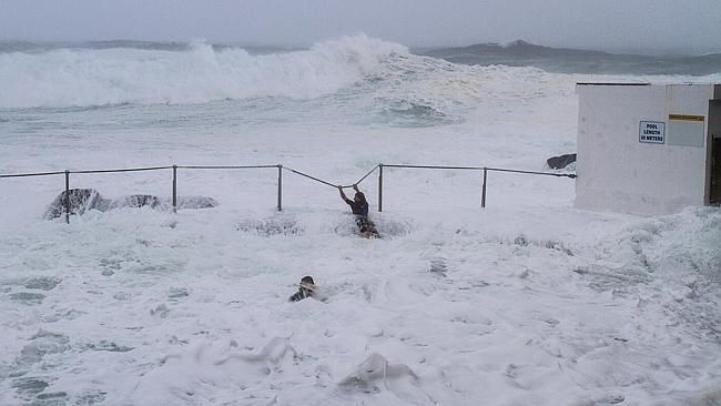 Two teenagers ignore the storm warnings, by risking their lives at Bronte Beach, Sydney,