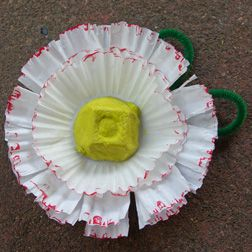 Mother's Day corsage: Paint egg carton section yellow and let dry. Have children cut into the ruffled sides of the liners, from the edge to where the ruffled part ends. They can make cuts about 1/2″ apart, or make designs or whatever they'd like. Run red marker around edges of each liner. Stack liners and secure in center with stapler or glue. Bend pipe cleaner into leaf shapes and secure on back with stapler or tape. Glue or tape yellow egg carton section to center.