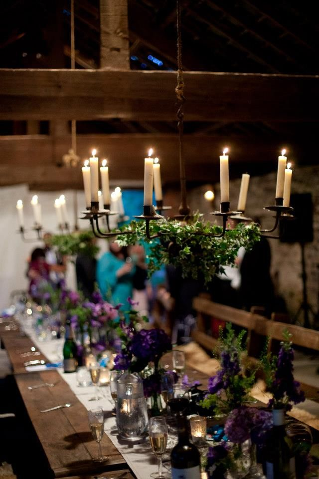 Tables decorated with iron chandeliers, ivy and flowers - Dewsall Court weddings in Herefordshire