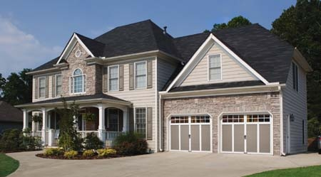 If 40% of your home's exterior is taken up  by your garage doors, make them interesting. Clopay Coachman Collection steel and composite carriage house doors Design 12, SQ 24 windows in Sandtone with white overlays. www.clopaydoor.com.