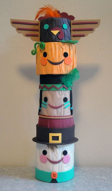 Thanksgiving totem pole craft for kids, made from empty food cans covered in tissue paper and decorated with cut craft foam and feathers. Copyright Pamela Maxwell 2013