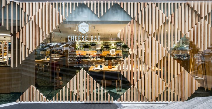 A modern cheese bar in Barcelona full of colorful details, wooden elements, and diamond patterns complete with a three-dimensional facade.