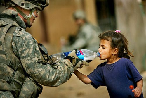 1st Battalion, 38th Infantry Regiment from Fort Lewis, Wash., offers an Iraqi girl a sip of his soda during a routine patrol through the streets of Baquoba. (Stephen M. Katz | The Virginian-Pilot) #military