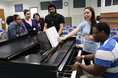 Impromptu sing-alongs are part of the energy during meetings. Pictured are singer Celina Hicks and accompanist Irvel Jean; around the piano are, from left, Dherey Santiago, Elisa Duncan, Marisa Bechtle and Dwayne Derry.