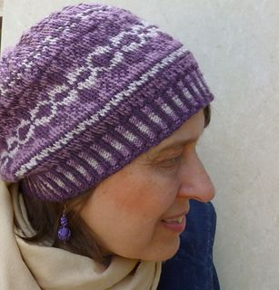Winter Arabesque Hat has a slightly slouchy look. Bands of motifs in three colors complement the corrugated ribbing.  The pattern instructions are clear and easy to work, taking all the stress out of knitting a colorwork hat. The pattern features detailed written instructions, photos, and complete charts for each size.