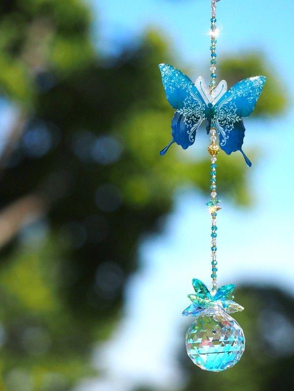 サンキャッチャーは、太陽の光をお部屋にたくさんの小さな虹のように運びこむお部屋の光のアクセサリーです。そのサンキャッチャーに世界一美しく、生きている宝石とまで言われているモルフォ蝶の碧い輝きをモチーフにしたhandcraft F…