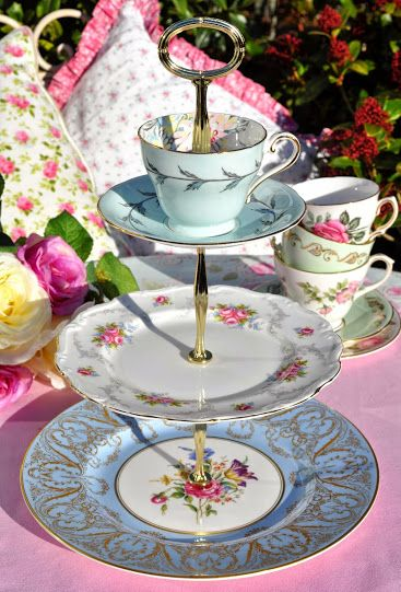 """Tranquility"" A fashionably mismatched vintage three-tiered cake stand with a teacup top.  This unique cake stand has been created from Royal Worcester, Royal Albert and Aynsley vintage bone china in shades of duck egg blue, with pretty floral patterns and gold gilding.  The teacup and saucer top tier was made in England by Aynsley. Bone china. Decorated with a delightful duck egg blue glaze and leaf pattern. On the inside a large chrysanthemum flower. Hand painted over transfer print.  The…"