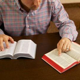 En mand sammenligner to bibeloversættelser