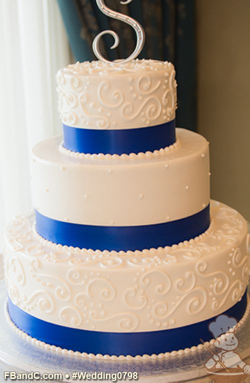 """Design W 0798   Butter Cream Wedding Cake   14""""+10""""+6""""   Serves 125   White Buttercream Icing, Hand Piped Scrolls & Swiss Dots, Royal Blue Ribbon   Standard Pricing"""