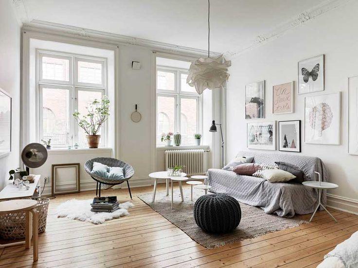 светлая гостиная в скандинавском стиле, натуральные деревянные полы, белые стены, вязаный плед