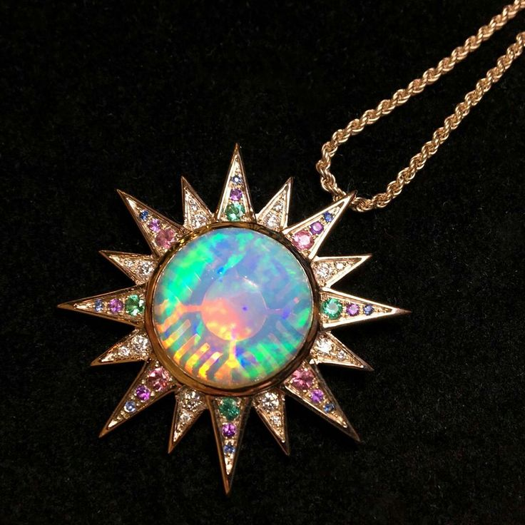 @thejewelleryed. Let this Venyx pendant light up your life. Multi-coloured gemstones highlight the splashes of colour of the spectacular Ethiopian opal.