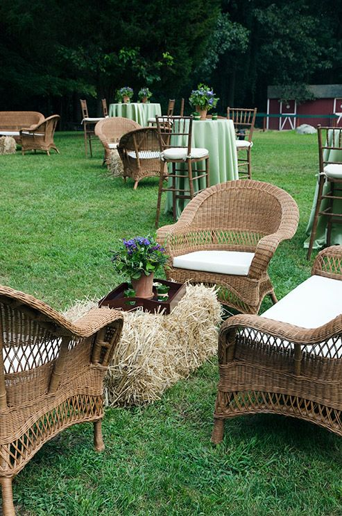 A lounge area is complete with wicker furniture and a bale of straw- turned cocktail table. Perfect for a County Wedding