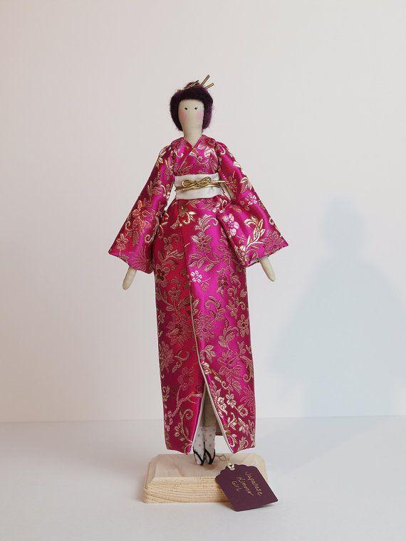 Chica Kimono japonés está tan de moda y lujo en su kimono rosa caliente vibrante. Ella tiene un aire de misterio e intriga sobre ella. Su kimono está forrado en satén de color crema. El mismo satén se utiliza para su obi o faja, y un hermoso obijime oro o cinturón, mantenga en su lugar. En el pelo de color rosa oscuro, dos palos de kanzashi mantener su pelo en lugar como en una cadena de oro. En los pies, que lleva calcetines blancos con zapatos rosa de lunares y geta. Se ve majestuoso y…
