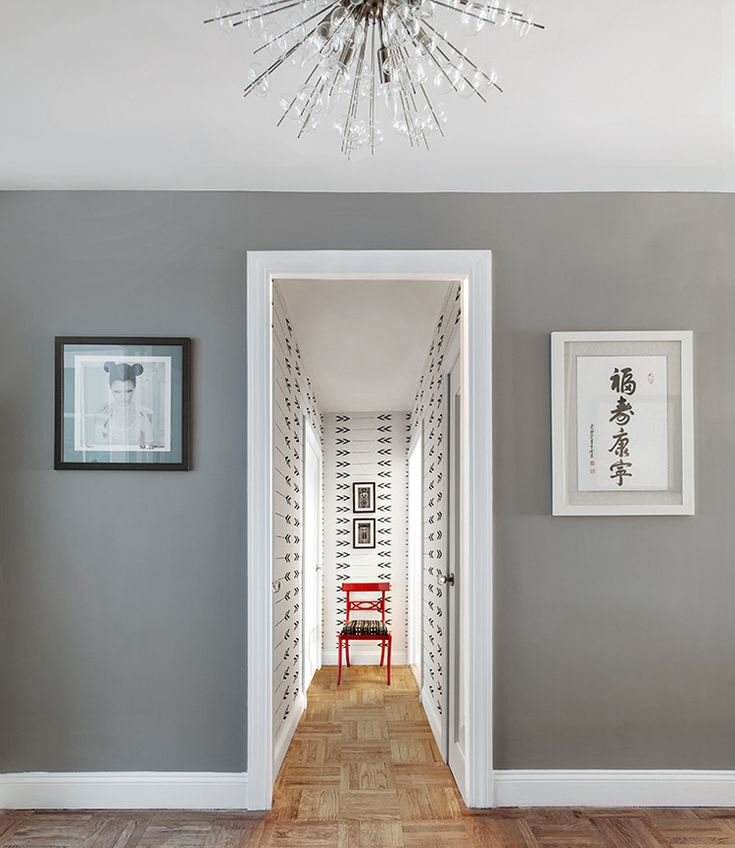 Gray walls with cool white trim give way to a wallpapered hallway in the midcentury modern apartment on either side of the door frame asian inspired